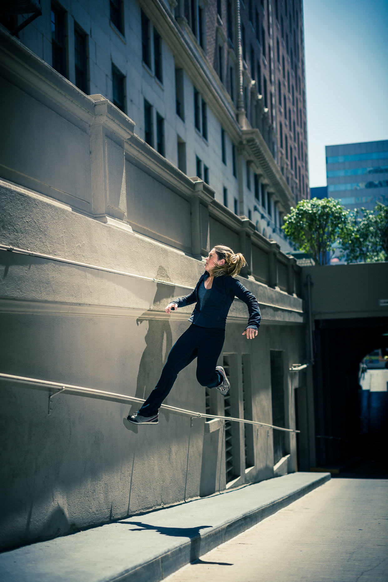Luci Romberg freerunner parkour athlete floating off a concrete wall in downtown LA by andy batt