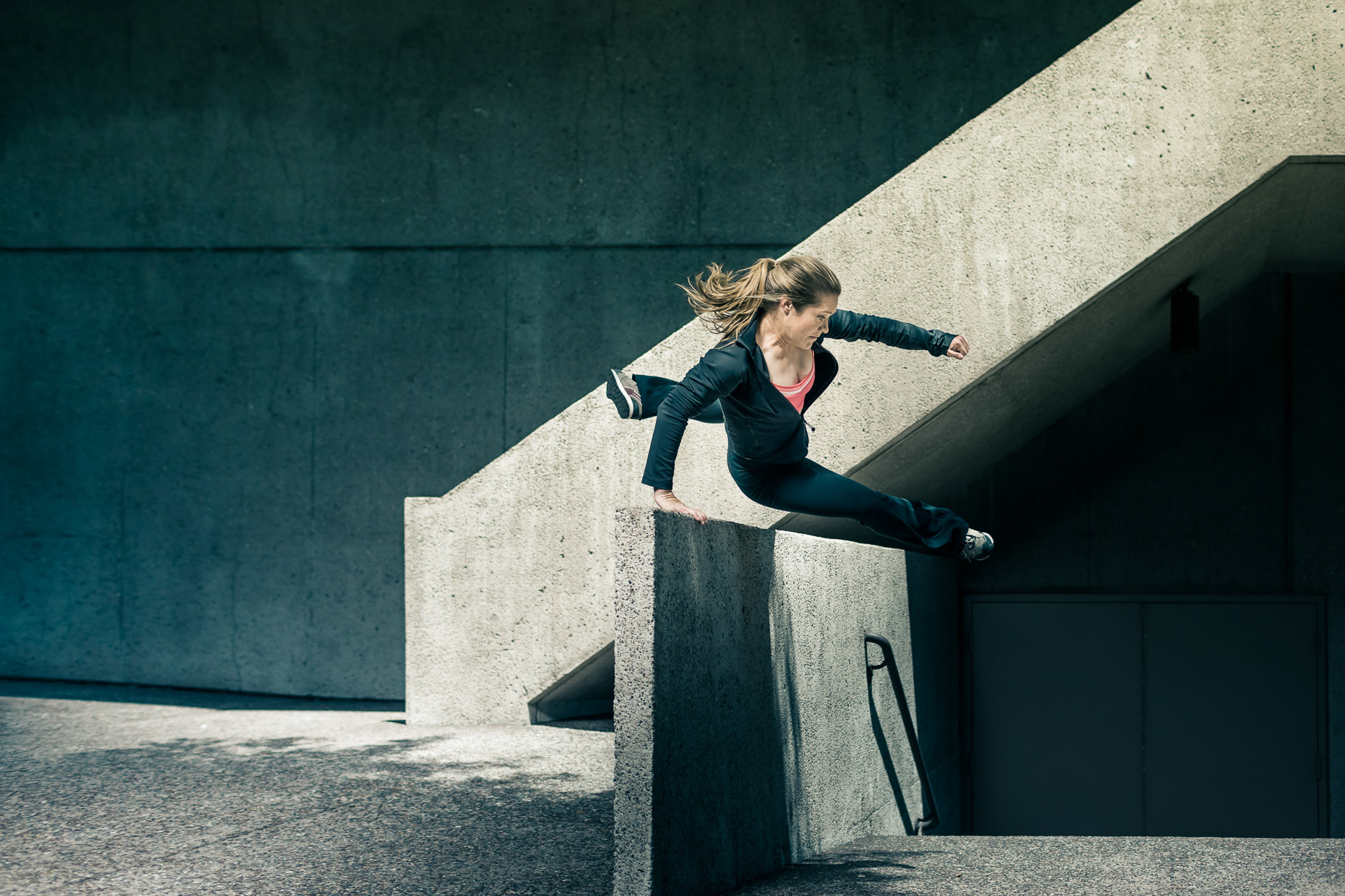 Luci Romberg freerunner parkour athlete leaping over concrete barrier wall in downtown LA by andy batt