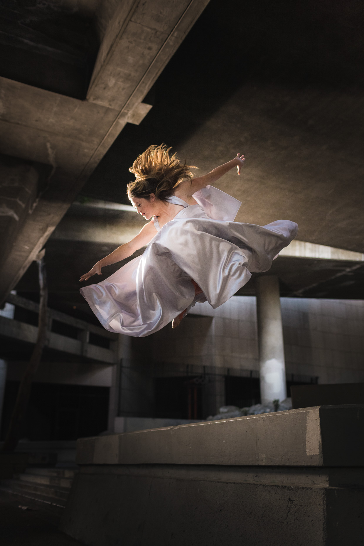 Luci Romberg freerunner parkour athlete in evening gown flying through the air under a bridge in downtown LA by andy batt