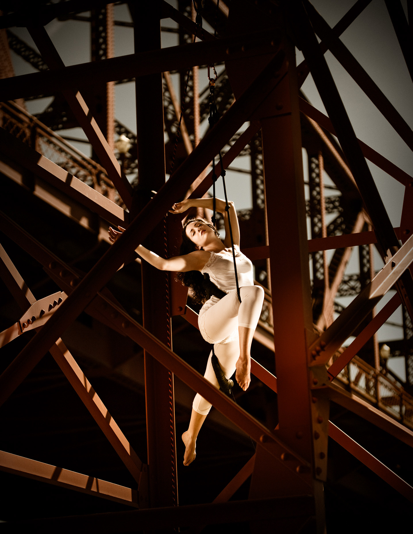 trapeze artist performing from Broadway Bridge with artist Sy Parrish in white leotard  by andy batt