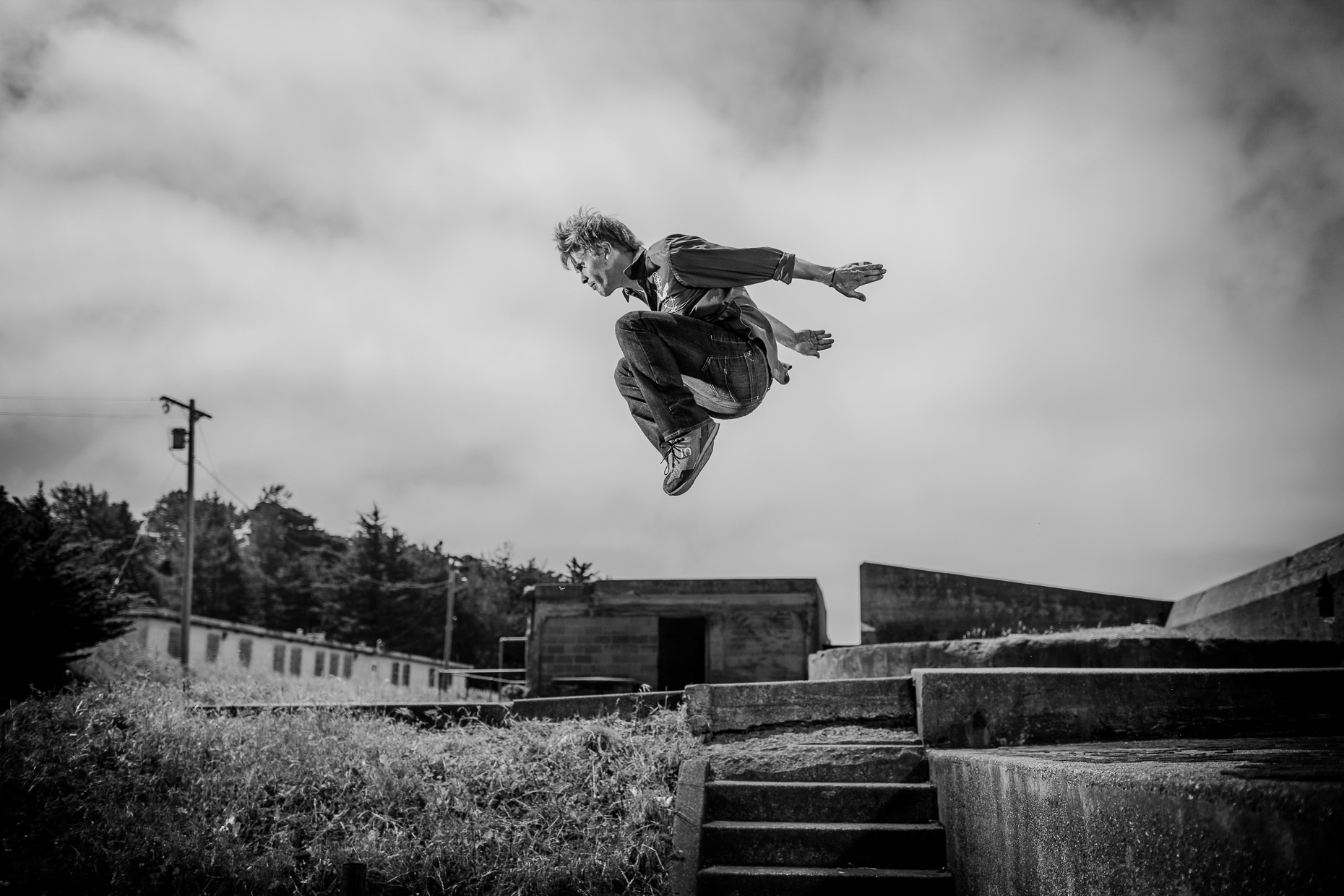 parkour freerunner athlete Brian Orosco flys between buildings at the Presidio army bunkers by andy batt