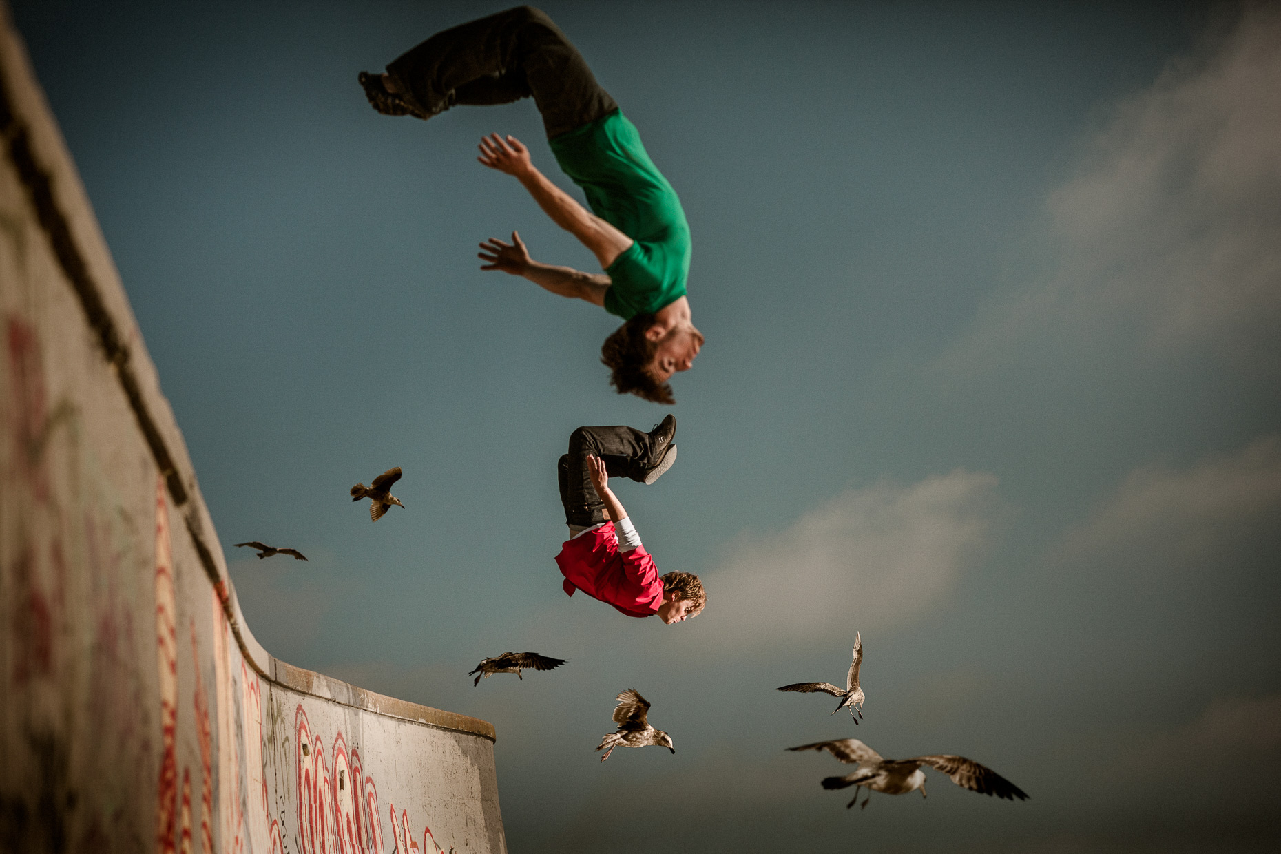 Parkour freerunner athletes Brian Orosco and Tyson Cecka flip over a concrete wall as seagulls fly by them