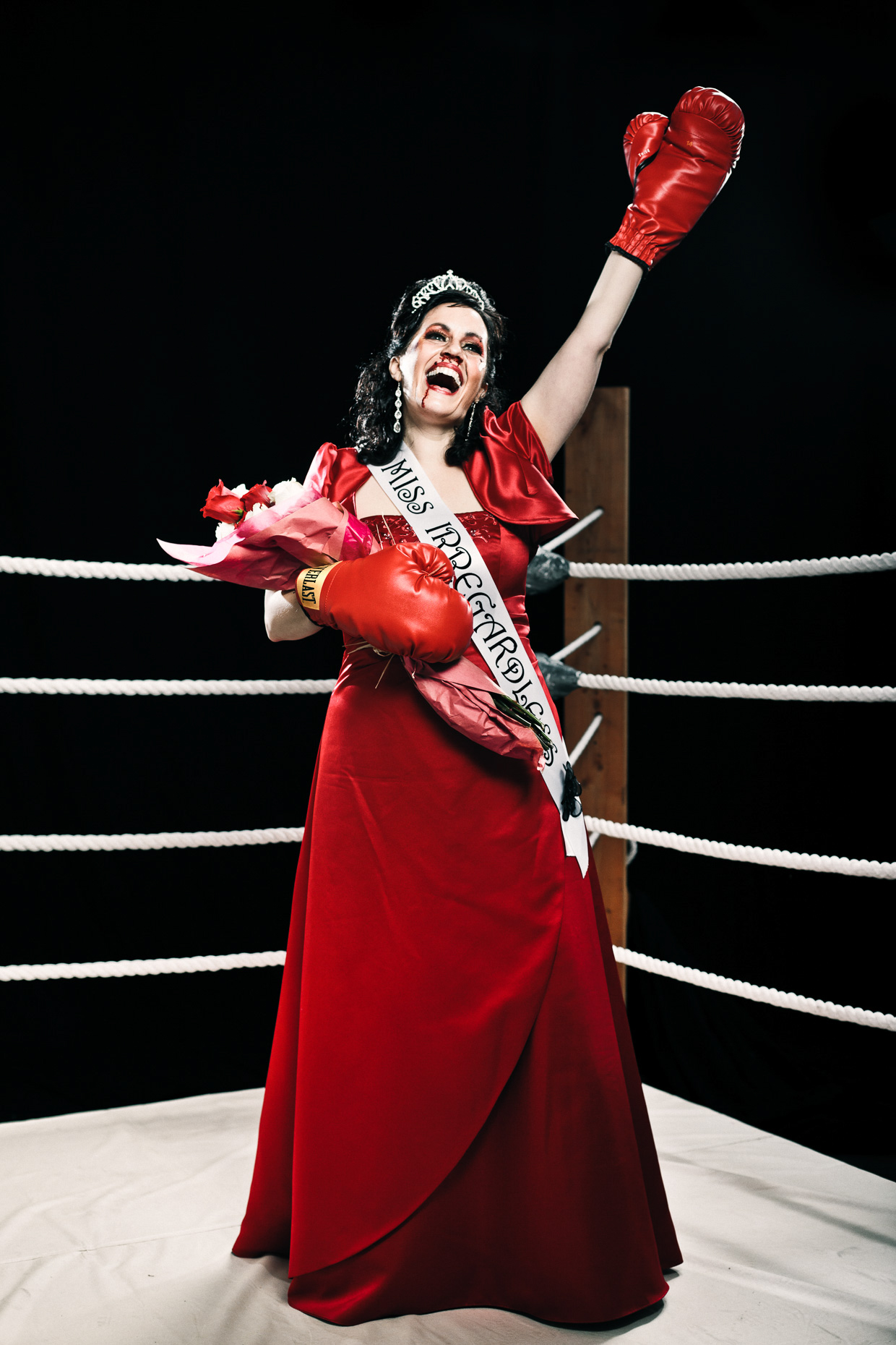 "Editorial portrait of Stacey Hallal as a beauty pagaent queen in the  ""Miss Irregardless"" boxing talent competition at the Curious Comedy Theater in Portland, Oregon. Poster art by Andy Batt"