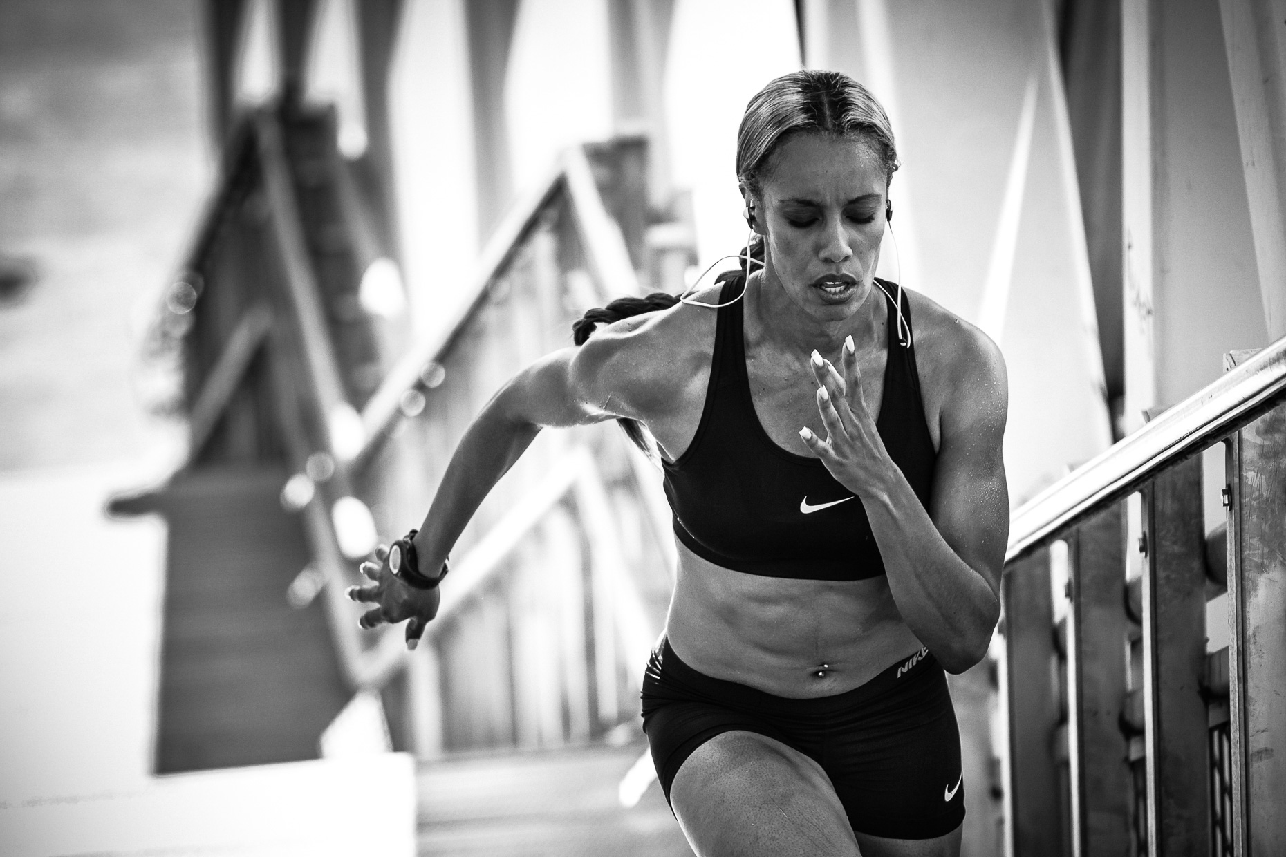 B&W image of Olympic track athlete Carol Rodriguez running up stairs along the Portland Esplanade by Andy Batt for Monster iSport