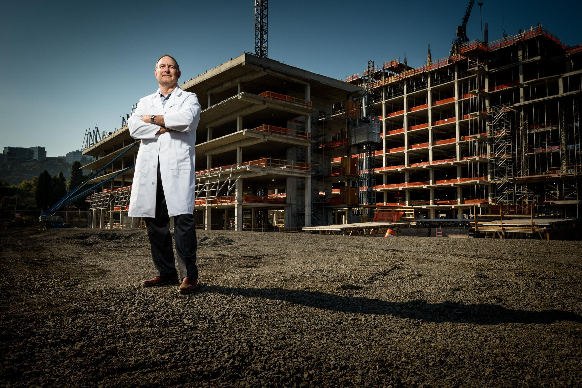 Full body environmental portrait OHSU Cancer researcher Joe Gray at the construction site of a new research facility for Portland Monthly Magazine by Andy Batt