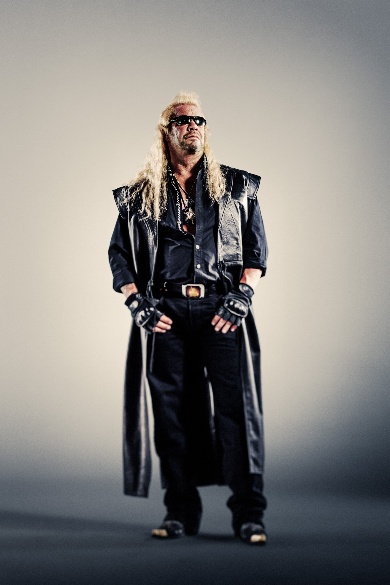 Full body editorial portrait of Dog the Bounty Hunter in all leather and his signature boots for CMT reality tv by Andy Batt