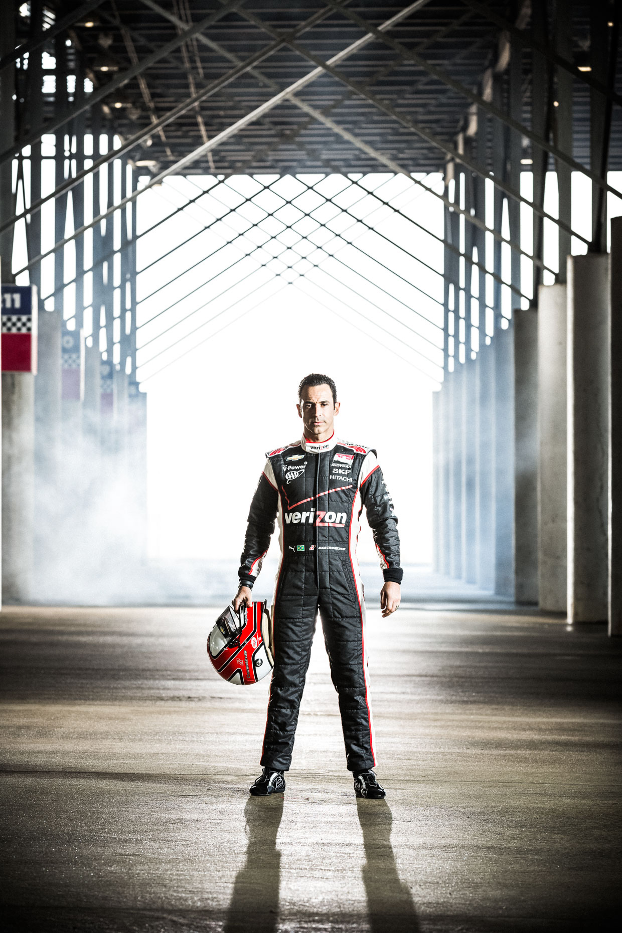 Dramatic full body portrait of athlete Helio Castroneves standing and holding helmet  IndyCar Driver Team Penske Garage Charlotte Motor Speedway below bleachers.  by Andy Batt