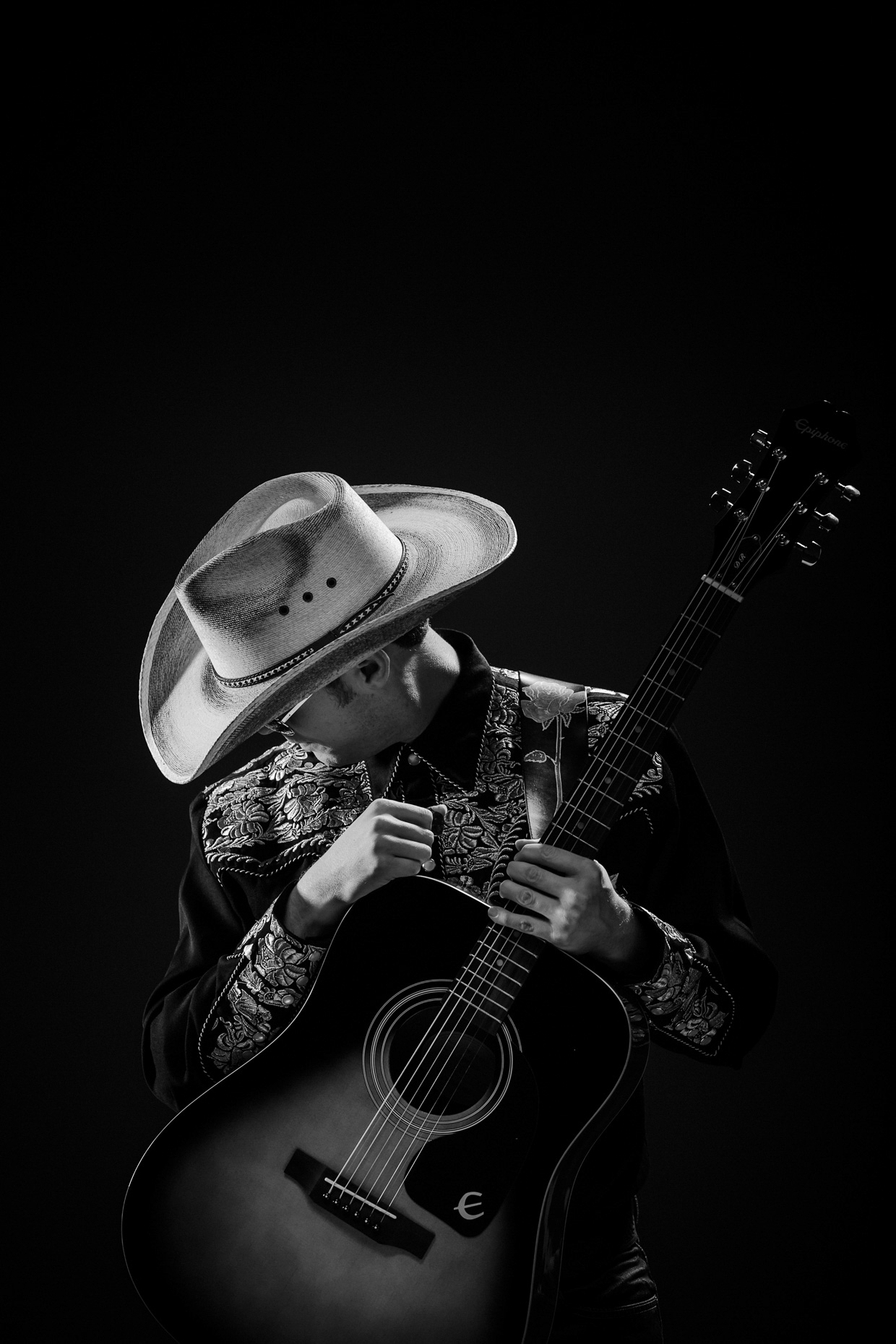 Musical artist Chase Padgett in a pensive pose wearing a cowboy hat and hoding his guitar for poster art of his one man show,  Nashville Hurricane by Andy Batt