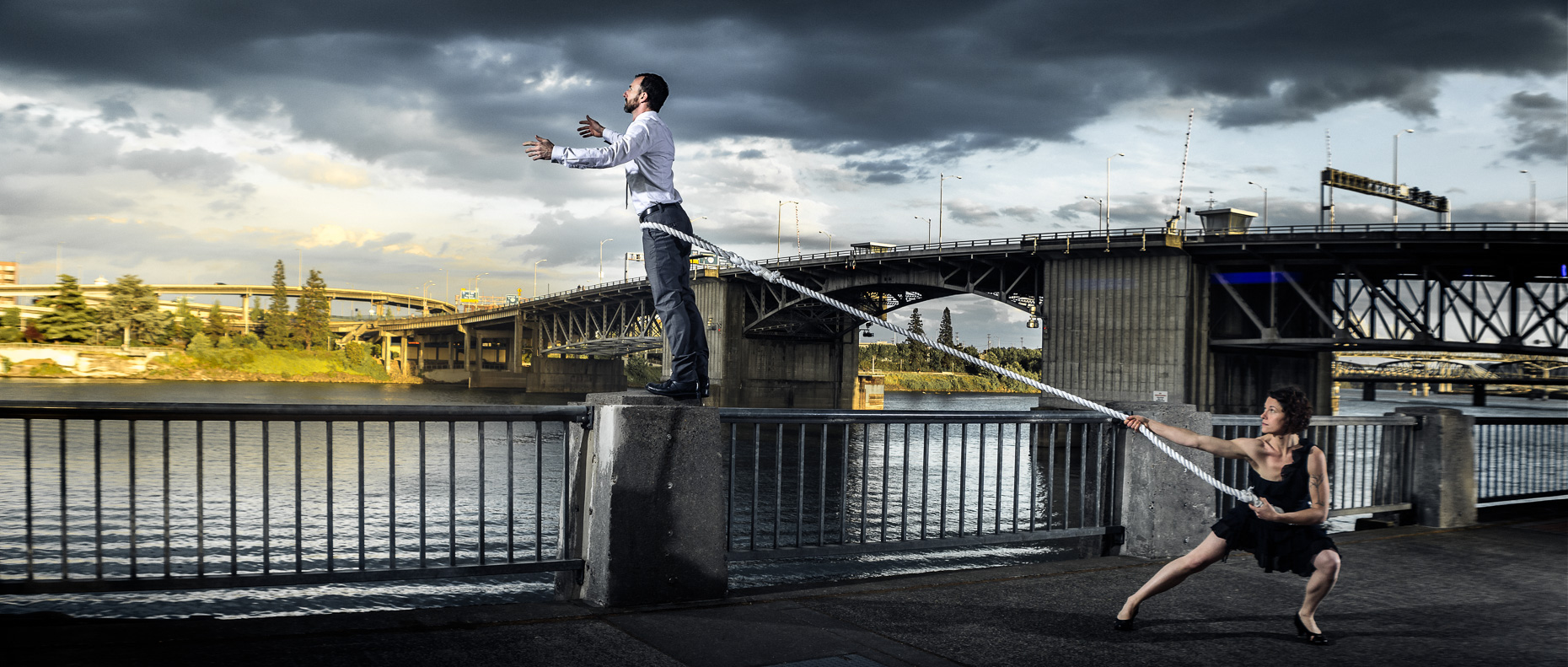 In this scene, Modern dancers Noel Plemons and Rachael Lembo practice social distance in this award-winning image next to the Morrison Bridge. Noel is suspended by a rope and reaches towards the opposite bank of the Willamette River and Rachael keeps the tension on the the opposite end of the rope to stop Noel from falling in. By Andy Batt