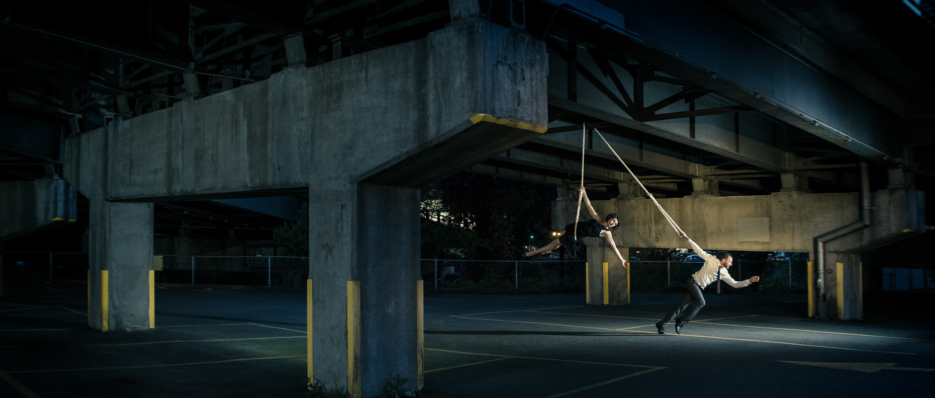 In this scene, Modern dancers Noel Plemons and Rachael Lembo practice social distance in this award-winning image under Morrison Bridge. Rachael is suspended by a rope and Noel keeps the tension on the the opposite end of the rope by Andy Batt