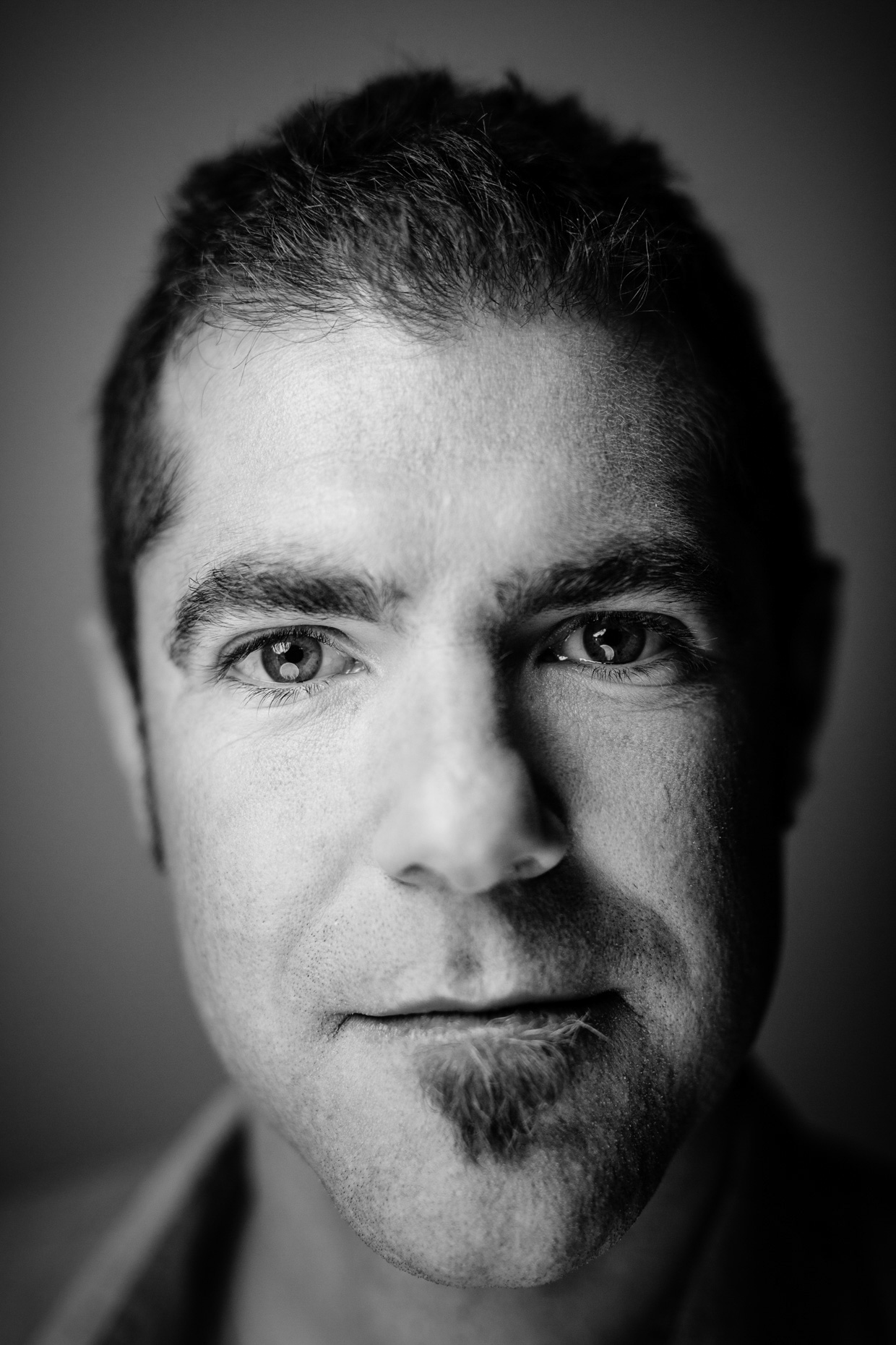 Tight B&W portrait of John Waller of Uncage the Soul Films, documentary filmmaker. by Andy Batt