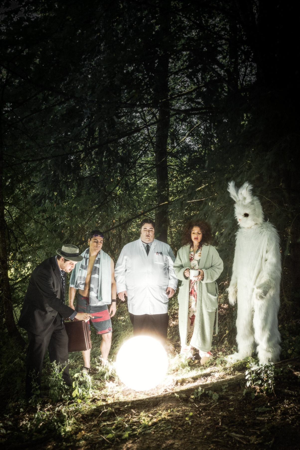 Moody scene of sketch Comedy actors Jason Rouse, Lori Ferraro, Ted Douglass, Andrew Harris and Tony St Clair in Wonderland Sketch Comedy. The performers surround a glowing white ball. The Donnie Darko rabbit is there too. Poster art by Andy Batt
