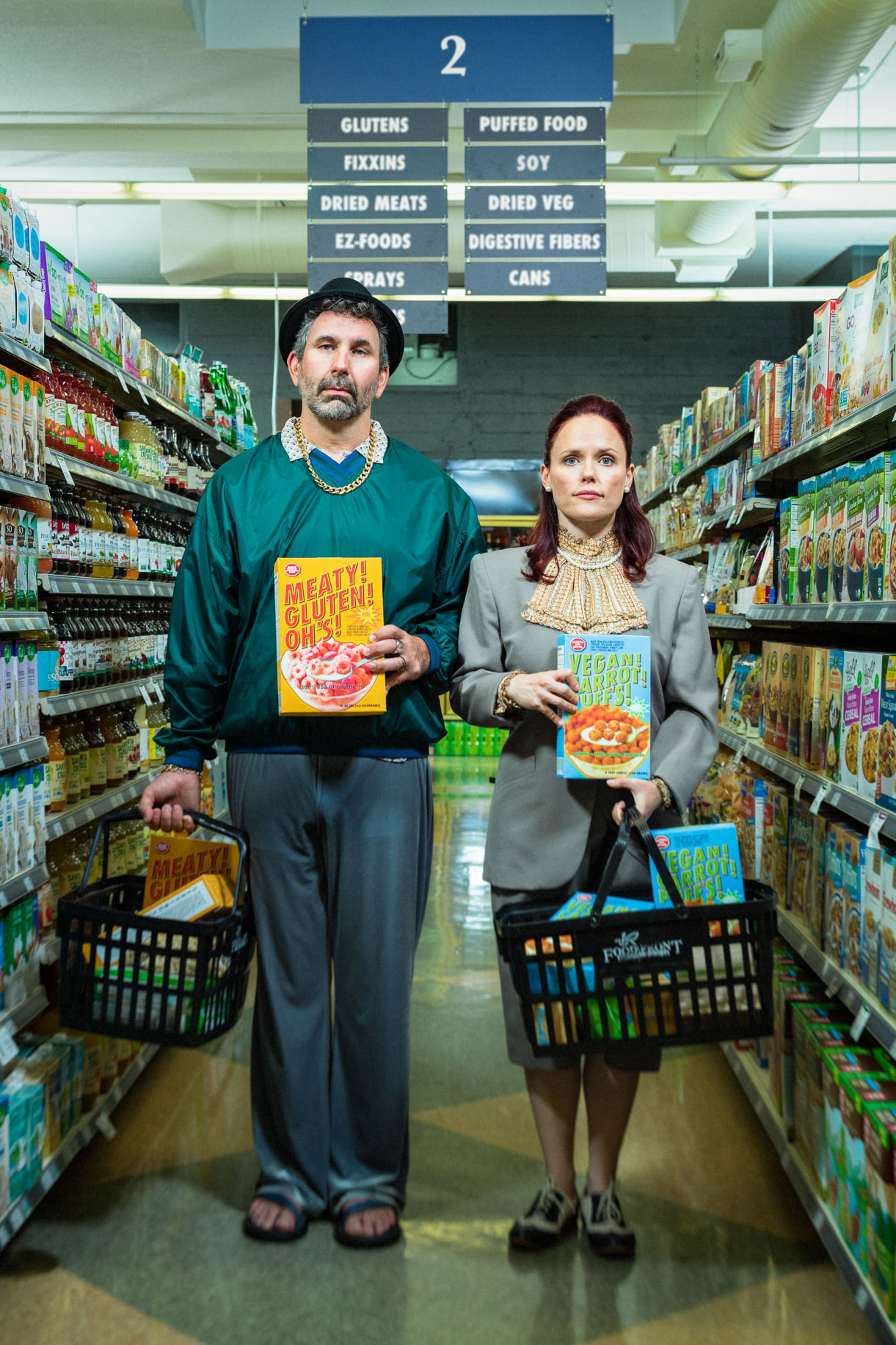 Entertainment portrait of Drunk History actor Craig Cackowski and wife Carla Cackowski for Orange Tuxedo improv. Poster art of the couple standing in aisle 2 of a grocery store holding boxes of cereal. Photo by Andy Batt
