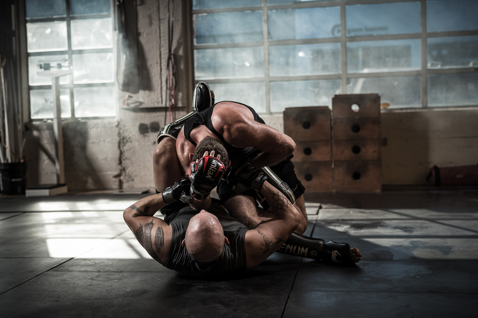 MMA athletes Jose Rogriguez and Will Hatcher  training in a crossfit gym by. The fighters grapple on the floor during training in a crossfit gym by Andy Batt