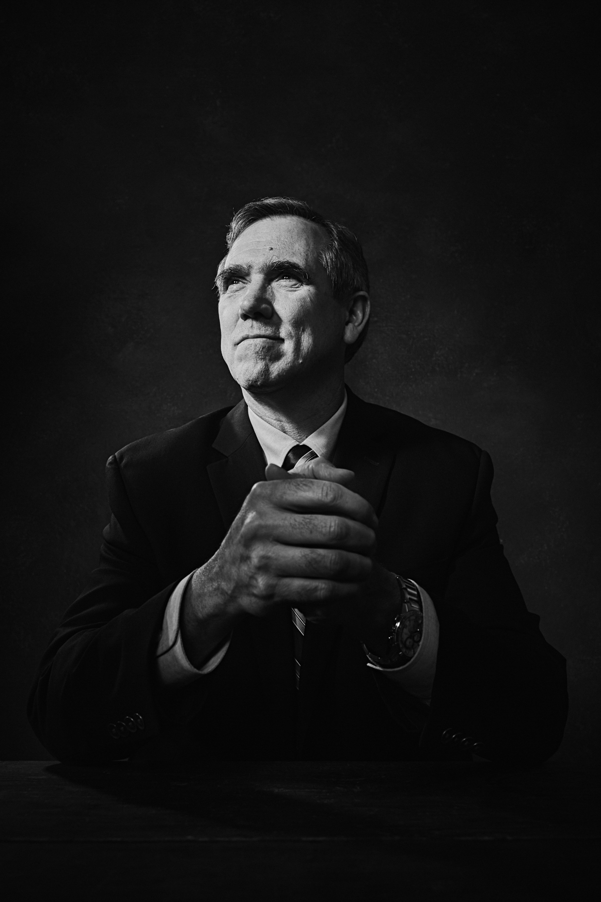 B&W Editorial portrait of Oregon senator Jeff Merkley in a formal pose holding his hands thoughtfully for Portland Monthly Magazine by Andy Batt