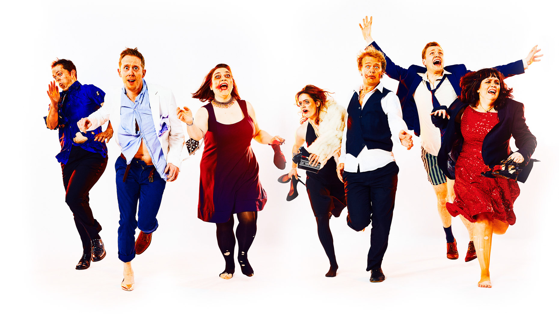 Group entertainment portrait of Improv performers Chad Parsons, Chase Padgett, Katie Beherns, Laura Sams, Matt Lask, Stacey Halall, and Tyler Quinn in Curious Comedy Theater improv Dynamite. Poster art of the 7 performers running towards camera in a white studio, wearing dissheveled party clothes from a rough night on the town. Photo by Andy Batt