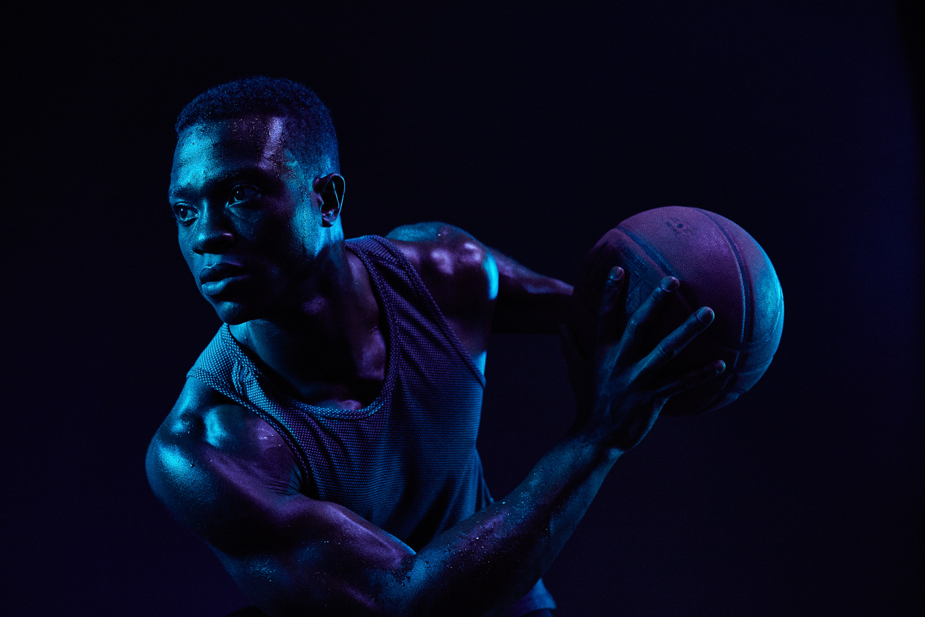 Nike basketball athlete David Kojo Aidoo by Andy Batt. The player holds the ball defensively in this dark scene lit with blue gels.