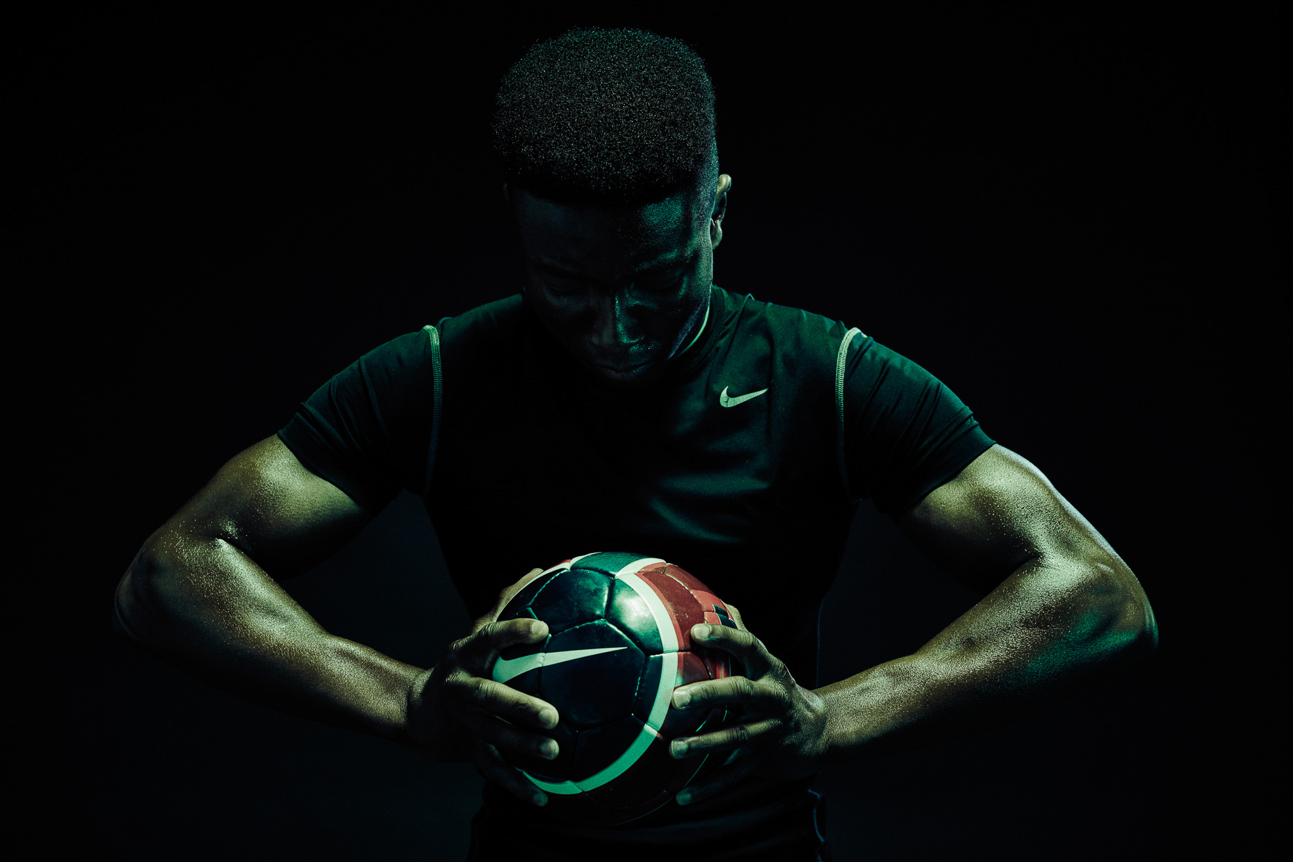 Nike soccer futbol Versace Sonachi holding the ball in a dark scene lit wiht green and blue gels by Andy Batt