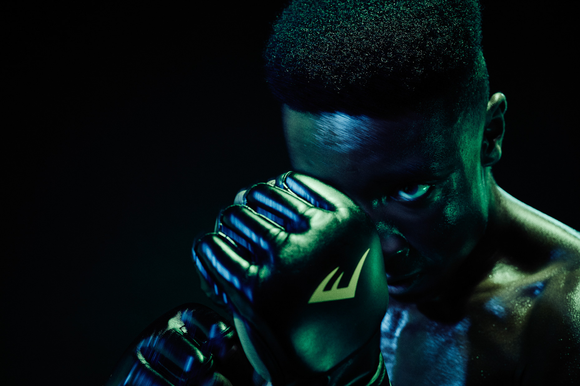 Nike boxing MMA Versace Sonachi guarding his face with boxing gloves in a dark studio lit with green and blue gels by Andy Batt