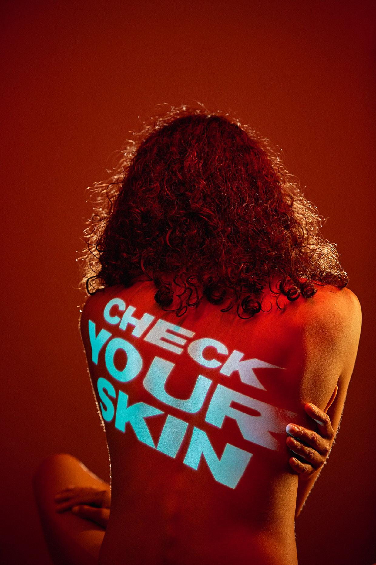 "Start Seeing Melanoma campaign for OHSU war on skin cancer with dancer Kayla. She is nude and turned away from camera and the words ""check your skin"" are projected onto her back. by Andy Batt"