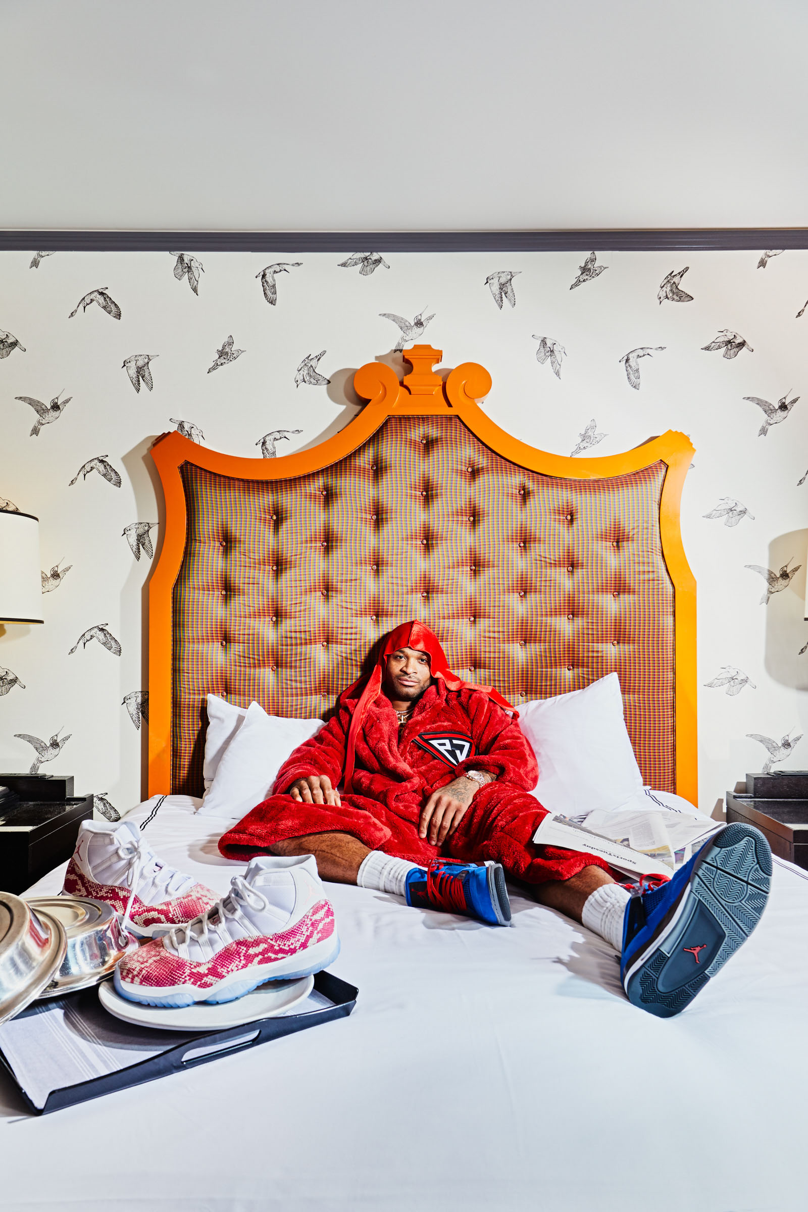 P.J. Tucker is the NBA's sneaker king, and a forward on the Houston Rockets. Photographed in bed at the Monaco Hotel, surrounded by his collection of collectible sneakers for Footwear News by Andy Batt.