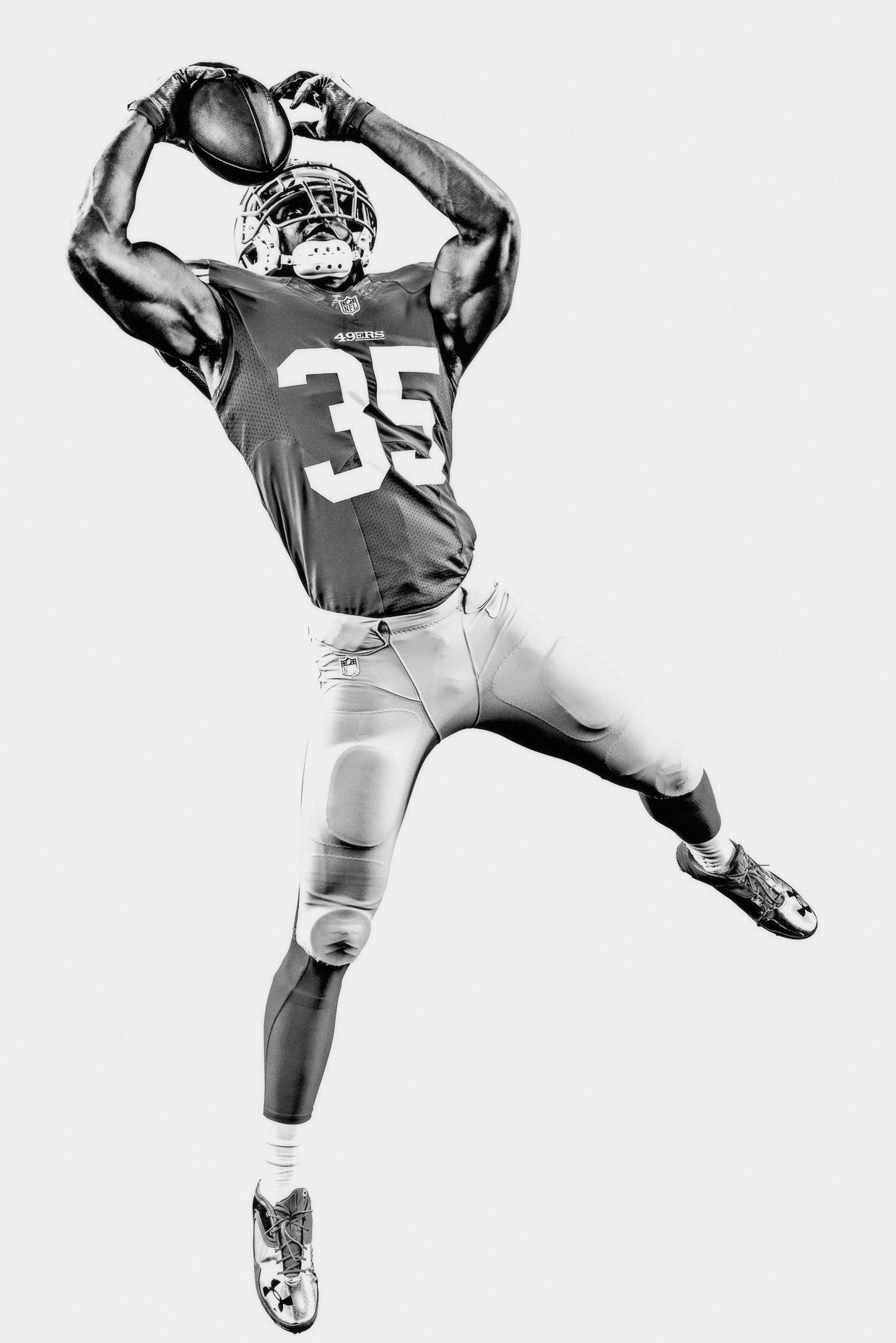 NFL Verizon Eric Reid catches football mid air San Francisco 49ers in a white studio by Andy Batt